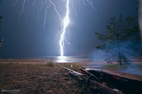 Фото Сильный разряд молнии над морем, попал в лежащее на берегу сухое дерево, вызвал его возгорание и появление легкого, синего дыма, автор NIKOLAY LOBKOV