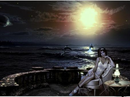 Фото Девушка-скрипачка сидящая в мягком кресле каменного ограждения, стоящего на морском побережье, на столике стоит горящая керосиновая лампа, лежит книга, рядом с креслом прогуливается кошка и стоит скрипка со смычком, на фоне заката, взошедшей планеты и взлетающих над волнами дельфинов