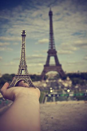 Фото В руке статуэтка эйфелевой башни / la tour Eiffel на фоне настоящей Эйфелевой башни, Париж, Франция / Paris, France