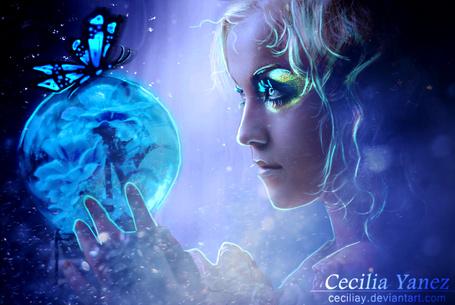 Фото Девушка смотрит на стеклянный шар, на котором сидит синяя бабочка, а внутри шара синие цветы, фотоарт ceciliay