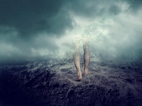 Фото Босые мужские ноги идут по земле рассыпаясь на мелкие частицы, которые уносит ветер, фотоарт