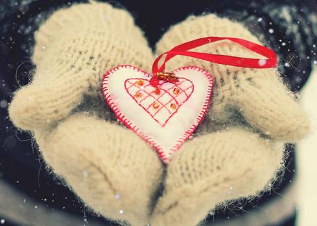 Фото Руки в вязаных перчатках держат сердечко на красной ленте