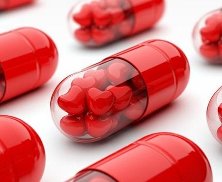 Фото Прозрачные красные капсулы наполненные сердечками на белом фоне