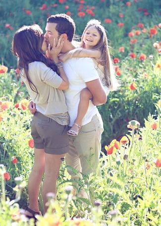Фото Девушка целует мужчину, который держит на руках девочку
