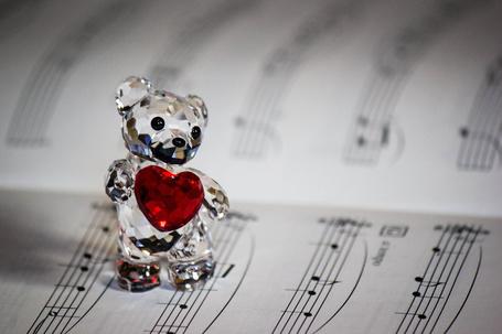 Фото Стеклянный мишка с красным сердечком стоит на нотах, фотограф d-VFX