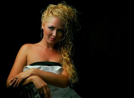 Фото Девушка блондинка с длинными волнистыми волосами и платье с декольте, стоит сложив руки перед собой на черном фоне