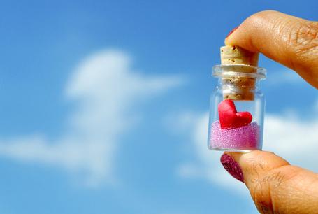 Фото Прозрачная баночка с розовыми гранулами и красным сердцем внутри, у девушки в руках, на фоне неба