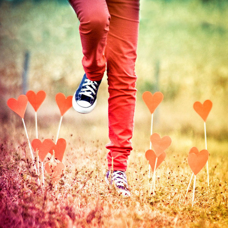 Фото Сердечки растут из земли вокруг бегущих ног в красных штанах и кедах