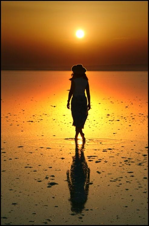 Фото Девушка в шляпе стоит в воде на фоне заката