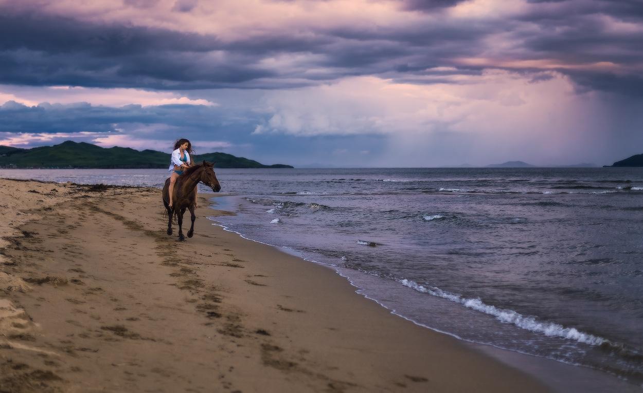 Фото Девушка в синем купальнике и белой рубашке, сидящая на гнедой лошади, идущей по песчаному морскому берегу на фоне пасмурного неба, автор Андрей Кровлин