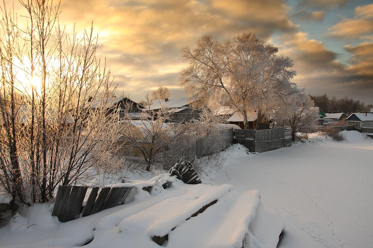 Фото Окраина небольшой деревни с домами, стоящими на заснеженной улице на фоне утреннего, восходящего солнца на пасмурном небосклоне, автор Александр Коротков