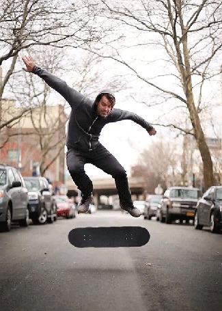 Фото Мужчина парит в воздухе, смотря, как крутится его скейтборд