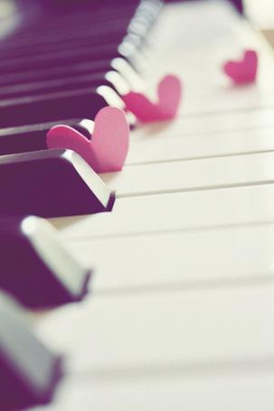 Фото Между клавишами пианино воткнуты бумажные сердечки