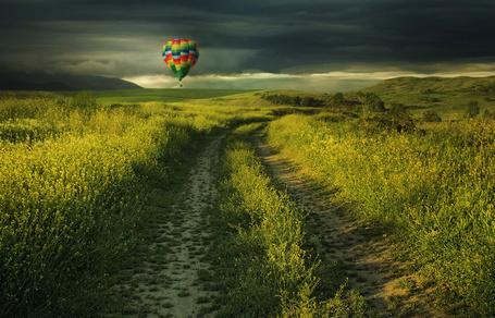 Фото Разноцветный воздушный шар парящий в воздухе над полем с цветущим рапсом, грунтовой дорогой на фоне пасмурного неба