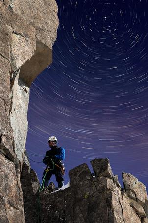 Фото Альпинист готовится к подъему на отвесную скалу на фоне звездных треков на ночном небе