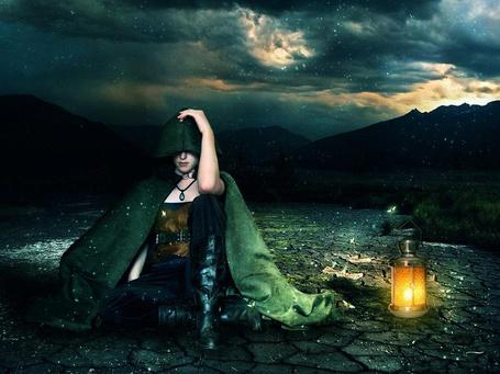Фото Девушка в плаще с капюшоном сидит на земле, рядом стоит горящий фонарь, автор PriscillaSantana