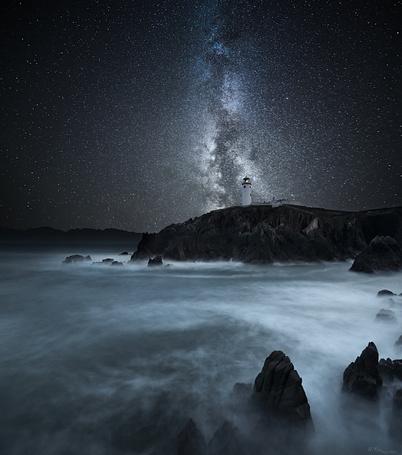 Фото Маяк, стоящий на скалистом морском побережье на фоне ночного, звездного неба и млечного пути