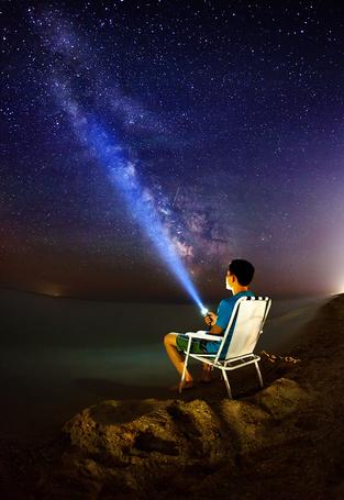 Фото Мужчина, сидящий на складном стуле на каменистом берегу моря, направил луч света от зажженного фонаря в ночное, звездное небо с млечным путем