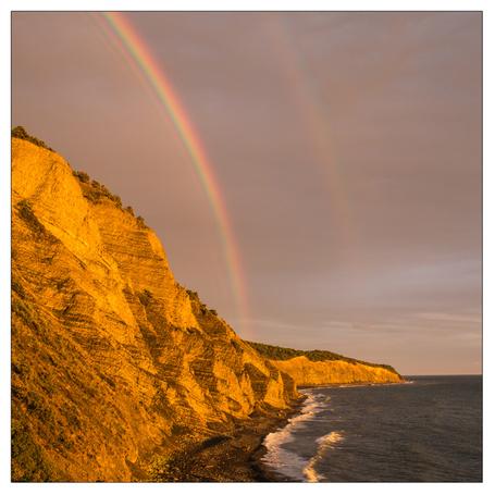 Фото Двойная радуга в пасмурном небе над скалистым, морским побережьем