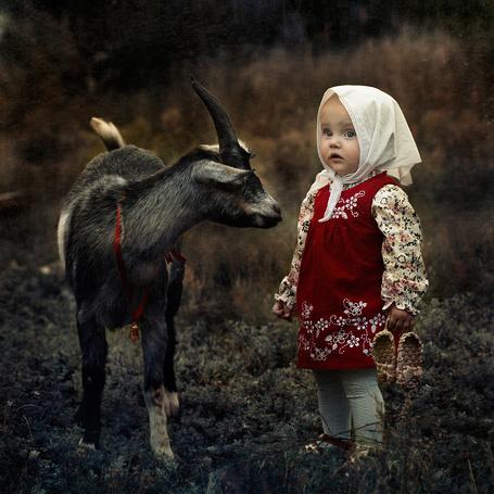 Фото Девочка в белом платке на голове, красном сарафане, держащая в руках плетеные лапти, стоящая возле черного козленка, фотограф Ярунин Олег