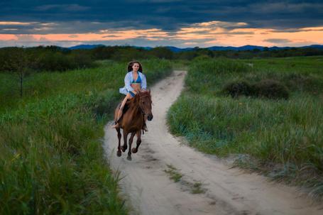 Фото Девушка в синем купальнике и надетой сверху голубой рубашки, скачущая на гнедой лошади по грунтовой дороге среди зеленой травы на фоне пасмурного неба, автор Андрей Кровлин