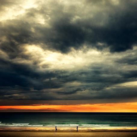 Фото Парень и девушка стоят напротив друг друга на фоне бескрайнего моря и грозного облачного неба, фотограф Ibai Acevedo