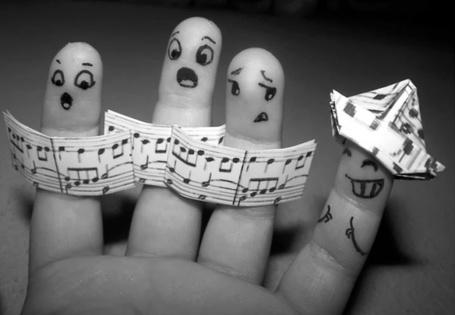 Фото На детской руке три пальца поют по нотам, а четвертый сделал из нотной тетради шапку
