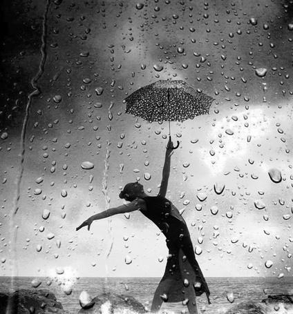 Фото Девушка стоит около моря с поднятым вверх зонтом на фоне дождевых капель