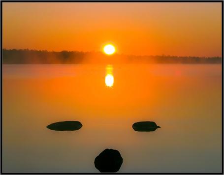 Фото Каменные валуны, лежащие у берега морского залива на фоне заходящего солнца на безоблачном небосклоне, автор Андрей Бурлов
