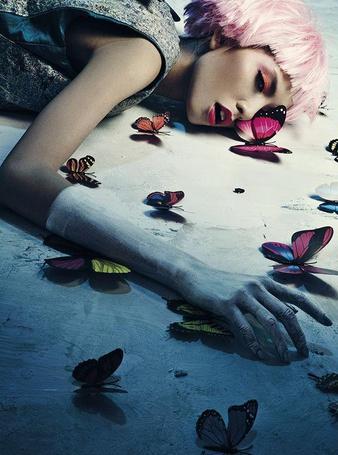 Фото Девушка с розовыми волосами лежит на полу среди бабочек