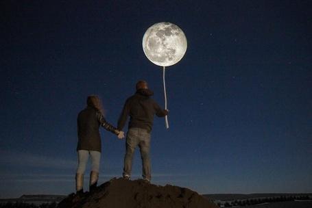 Фото Мужчина с девушка стоят на горе держась за руки, мужчина держит в руке шарик в виде луны