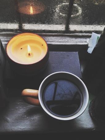 Фото Кружка чая и свеча стоят возле окна