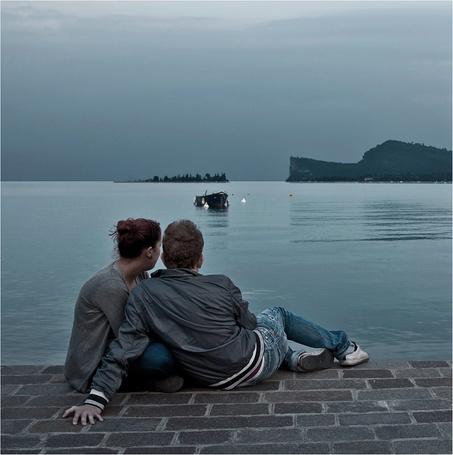 Фото Парень и девушка, тесно прижавшись друг к другу, сидящие на брусчатой морской набережной, наблюдают за лодкой, стоящей в воде напротив их на фоне пасмурного неба на вечернем небосклоне, автор Сергей Гаспарян