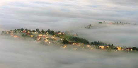 Фото Красивый поселок с каменными домами, стоящими в окружении деревьев на холмистой местности, окутанной густым, молочным туманом на рассвете, автор Robert