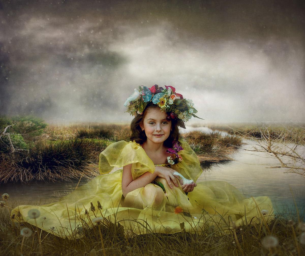 Фото Милая, темноволосая девочка с венком из цветов, сидящая на берегу водоема среди пушистых одуванчиков, держащая в руке маленькую белую птичку, автор Svetlana Melik-Nubarova