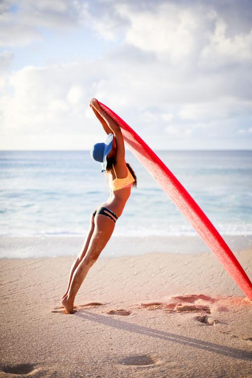 Фото Девушка придерживает доску для серфинга, стоя на морском берегу