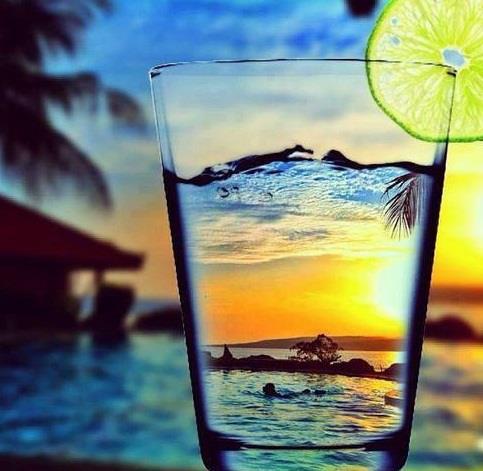 Фото Стакан с водой стоит на фоне моря, на краю стакана ...