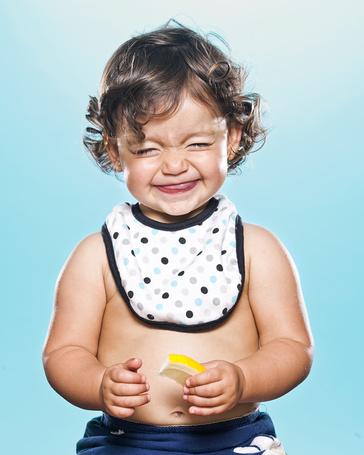 Фото Маленький мальчик со слюнявчиком на шее, держит в руке дольку лимона и улыбаясь, скривился от кислоты лимонного сока