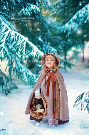 Фото Улыбающаяся, милая, светловолосая девочка, держащая в руке плетеную корзинку с цветами и виноградом, стоящая на заснеженной тропинке, среди елей, автор Полковникова Катерина