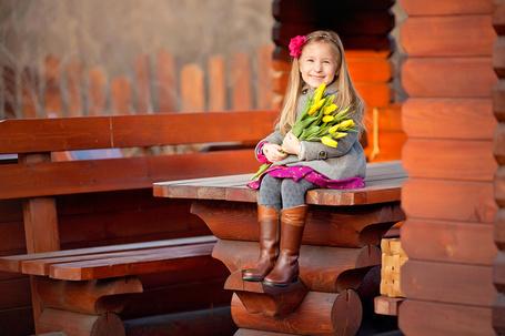 Фото Улыбающаяся, милая девочка, держащая в руках охапку весенних, желтых тюльпанов, сидящая на деревянном столике, стоящим возле дома, автор Юлия Зарх