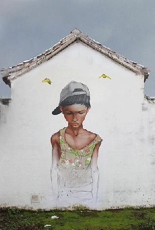 Фото Ожившее граффити на стене дома, в виде парня в майке и кепке, над которым летают птицы