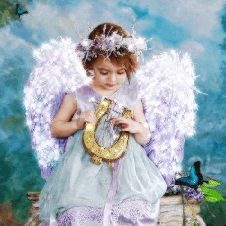Фото Девочка - ангел со сверкающими крыльями держит в руках небольшую арфу