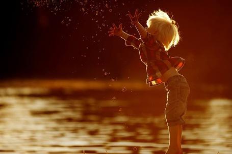 Фото Мальчик стоит в воде и перед ним брызги