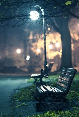 Фото Лавочка в парке, стоящая невдалеке от горящего фонаря
