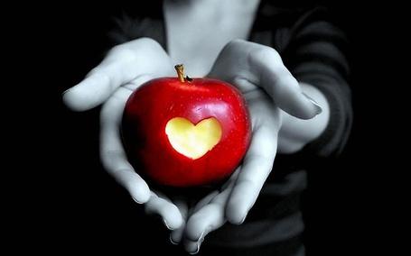 Фото Руки, протягивающие красное яблоко с вырезанным сердечком