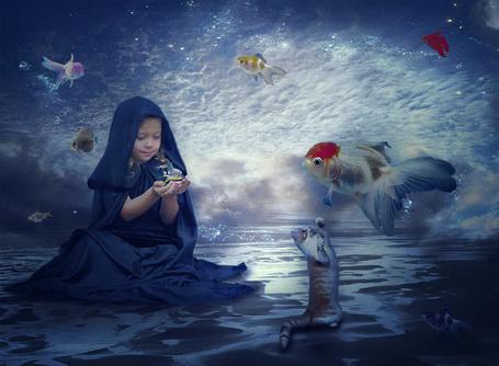 Фото Милая, белокурая девочка, сидящая на берегу моря, рассматривает экзотическую красивую рыбку над ее ладонями, рядом стоит кот, пытающийся лапой достать до рыбки над его головой, на фоне неба с перистыми облаками парят экзотические рыбы, автор Nataliorion