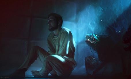 Фото Мужчина в смирительной рубашке сидит на полу, за его спиной монстр