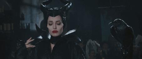Фото Актриса Анджелина Джоли / Angelina Jolie в роли Малефисенты / Maleficent, в одноименном фильме Малефисента / Maleficent, стоит рядом с вороном, улыбаясь