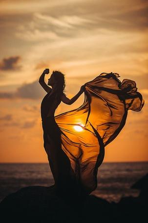 Фото Девушка стоит на камне на фоне заката