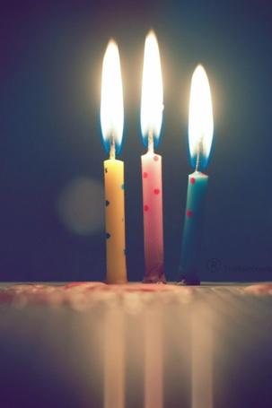 Фото Три горящие свечи разного цвета: желтого, розового и голубого